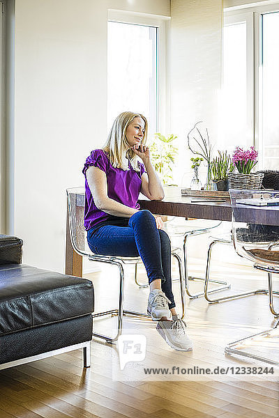 Pensive mature woman sitting at table at home