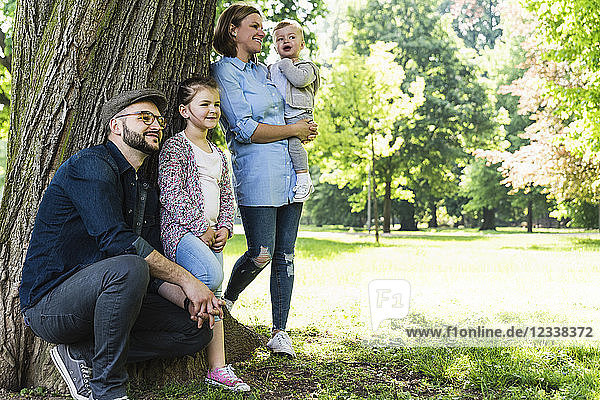Happy family under a tree in a park