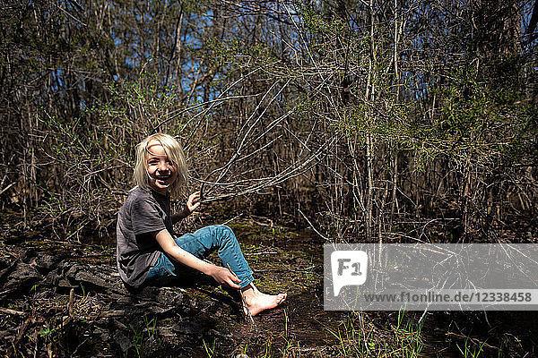 Porträt eines barfüssigen Jungen im Wald  der lächelnd in die Kamera schaut