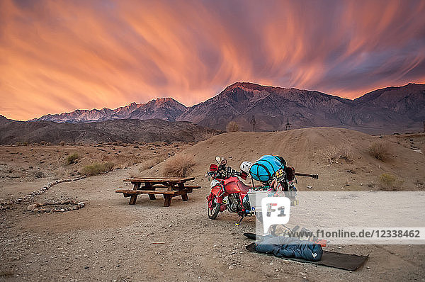 Part unloaded touring motorcycle parked at picnic area at sunset  High Sierra National Forest  California  USA