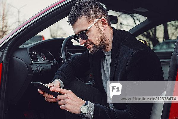 Bärtiger Geschäftsmann benutzt Mobiltelefon in Luxusauto