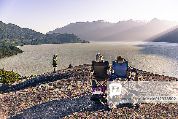 Friends relaxing in camping chairs on mountain ledge overlooking lake  Squamish  Canada