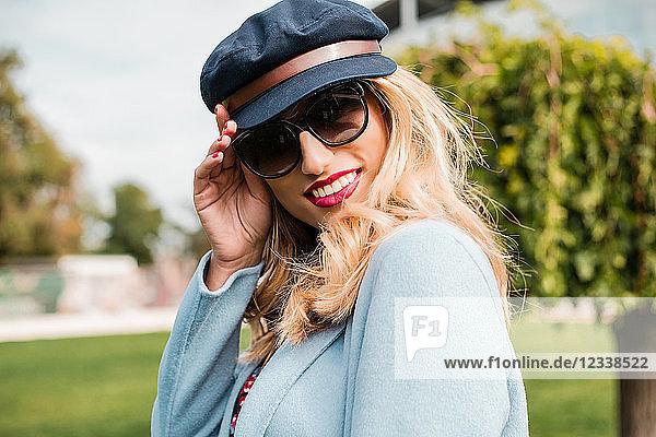 Porträt einer Frau mit Sonnenbrille und Bäckerjungenmütze  die lächelnd in die Kamera schaut
