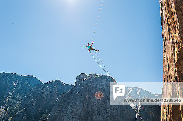 Person swinging mid air against blue sky on alcove swing at the base of El Capitan  Yosemite Valley  California  USA