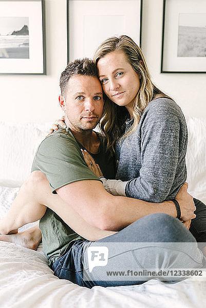 Frau sitzt auf dem Schoß des Mannes und schaut in die Kamera