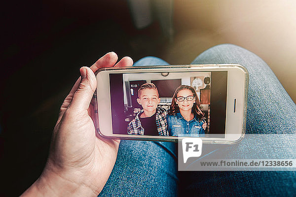 Mother holding smartphone with picture message of twin girl and boy,  personal perspective