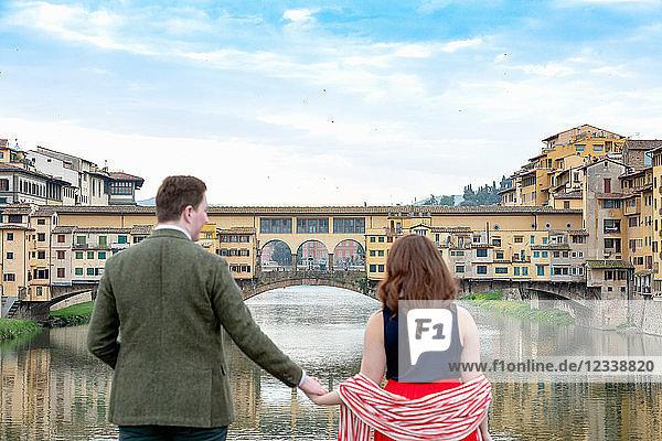 Junges Paar betrachtet Ponte Vecchio  die alte Brücke  Florenz  Toskana  Italien