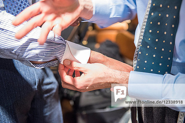 Tailor fastening shirt cuff of customer  cropped close up of hands