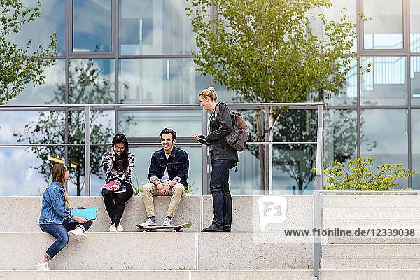 Vier junge erwachsene Studenten sitzen vor dem College auf einer Treppe und unterhalten sich