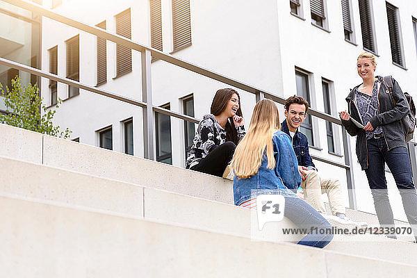 Vier junge erwachsene Studenten sitzen plaudernd auf einer Treppe vor dem College  Blick aus niedrigem Winkel