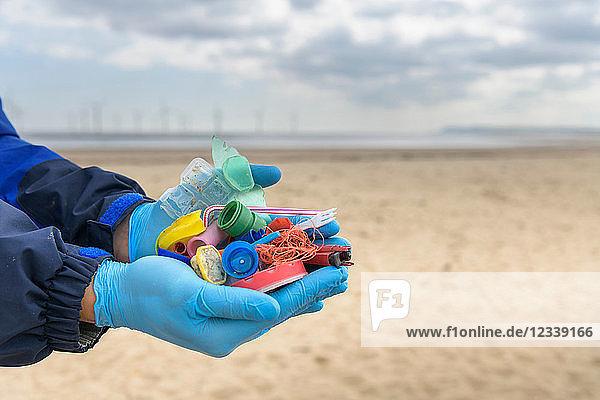 Mann hält Beispiele von Plastikbelastungen  die am Strand gesammelt wurden  Nordostengland  UK