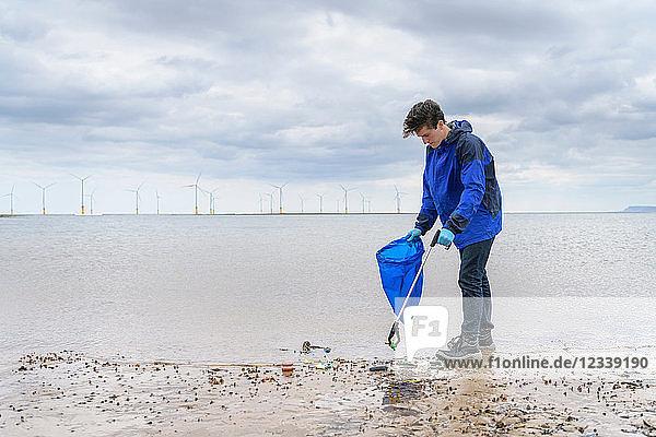 Mann benutzt Müllzerkleinerer  um am Strand gesammelte Plastikabfälle zu entfernen  Nordostengland  UK