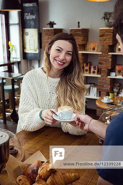 Junge Frau nimmt eine Tasse Kaffee vom Kellner