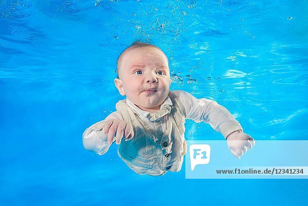 3 months boy in dress learning to swim underwater in the pool.