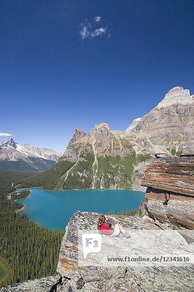Female hiker enjoying view from high lookout on lake ohara. Lake O`Hara area  Yoho National Park  British Columbia  Canada.