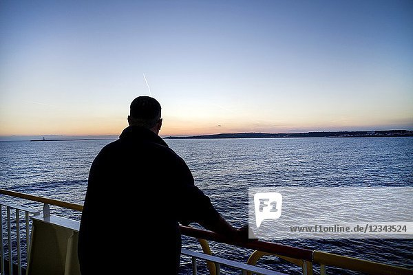 Silhouette of unrecognizable man on the deck of a ferry boat in port. Mediterranean Coast  Mahon  Menorca  Balearic Islands  Spain