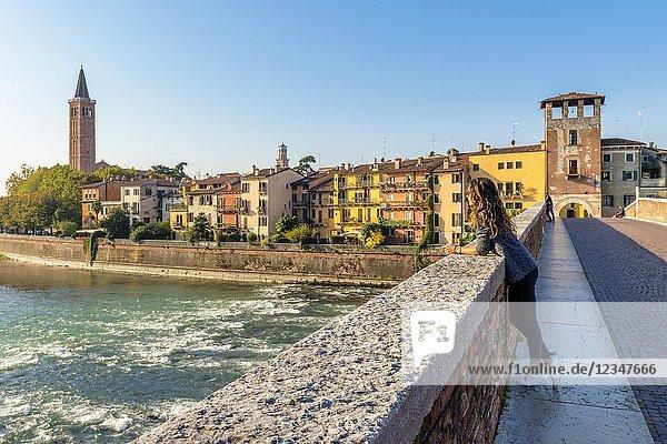 Tourist admiring the view of Verona old town from Ponte Pietra. Verona  Veneto  Italy.