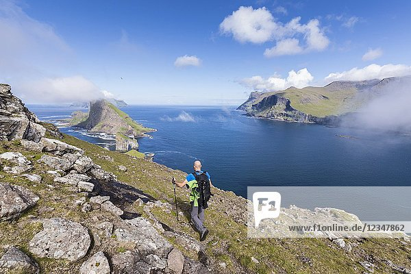 Hiker on cliffs overlooking Drangarnir rock  Vagar Island  Faroe Island.