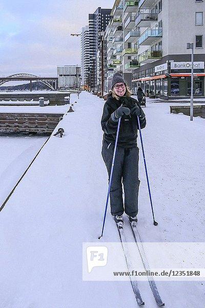 Winter and ice  Liljeholmskajen neighborhood. Woman cross country skis on the quaye. Stockholm  Sweden.