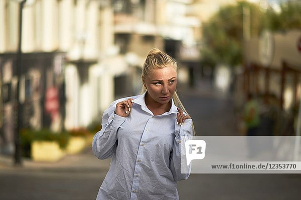 Portrait of confident woman in business shirt in summer sun  walking down the public road. Russian ethnicity. In holiday destination Hersonissos  Crete  Greece