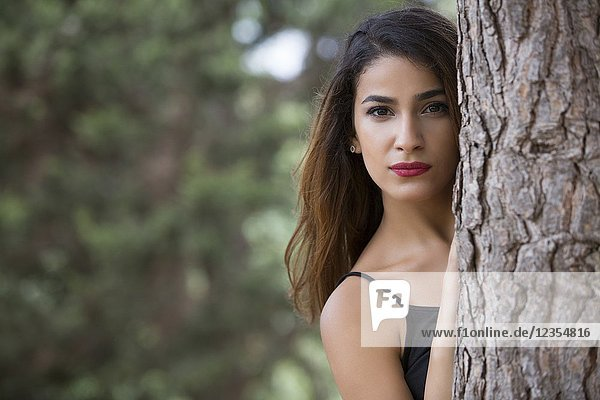 Beautiful young woman hiding behind a tree.