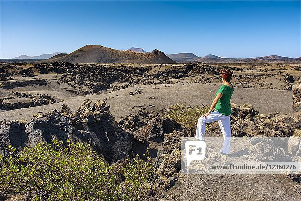 Tourist woman. Volcanic landscape  Timanfaya National Park. Lanzarote Island. Canary Islands Spain. Europe.