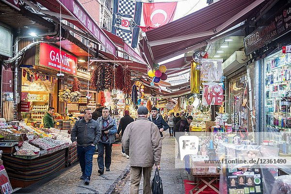 Awnings provide cover for shoppers as they walk along pathway lined with stores and stalls selling goods in outdoor market  Istanbul  Turkey.