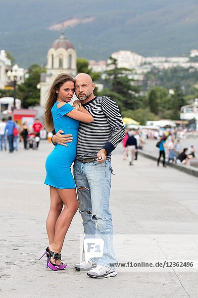 Couple of lovers having fun and taking photographs themselves with remote control on the promenade of Yalta  Crimea.