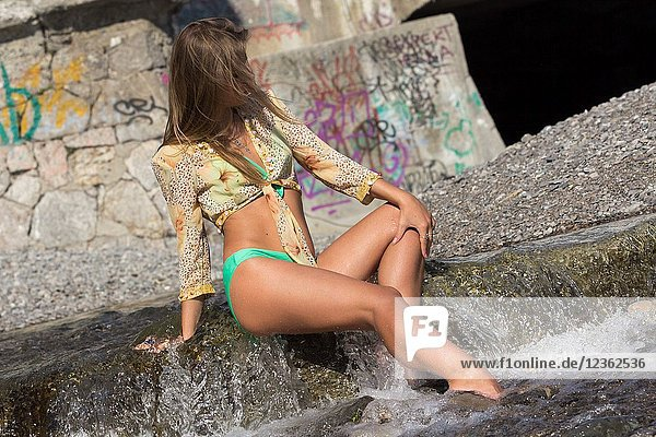 Sexy woman with a beautiful body wetting the feet on the river water's and posing sensually in Yalta  Crimea.