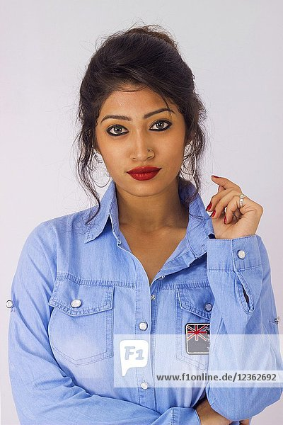 Close up of stylish woman in blue top with arm raised. Front pose.