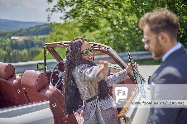 Woman waving to man while entering luxury car. Couple enjoying countryside adventure trip in luxury oldtimer. Turkish ethnicity. Blogger Adem Bayalan. Bavaria  Germany.