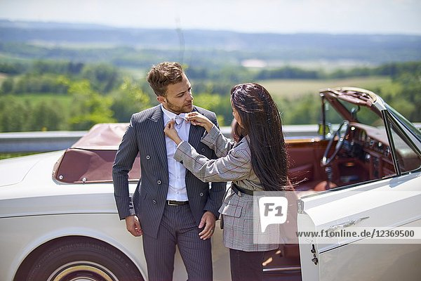 Woman fixing shirt of man in front of luxury car. Turkish ethnicity. High society. Blogger Adem Bayalan. Bavaria  Germany.