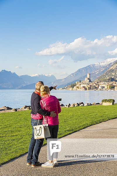 A couple of turists admiring Malcesine viewed from the lakefront on the eastern shore of Lake Garda  Verona province  Veneto  Italy.