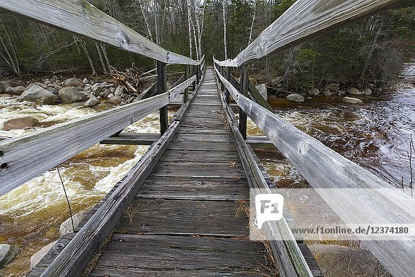 The Thoreau Falls Trail bridge  which crosses the East Branch of the Pemigewasset River  in the Pemigewasset Wilderness of New Hampshire. This bridge has a tilt to it that is visible in the photograph.