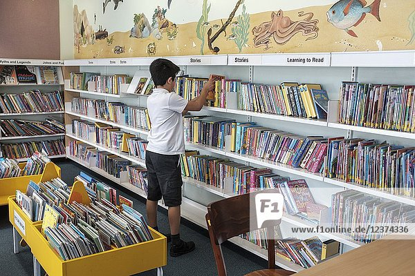 UK Surrey UK- 10 years schoolboy choosing books in public library.