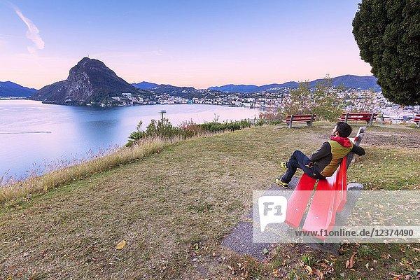 Man on bench on the shore of Lake Lugano  Parco San Michele  Lugano  canton of Ticino  Switzerland.
