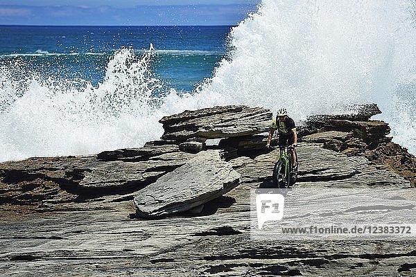 Mountainbiker mit Fatbike auf Klippe  Radtour am Die Plaat Beach  Nature Reserve  De Kelders  Gansbaai  Westkap  Südafrika