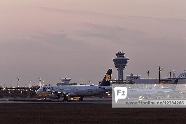 Lufthansa A321-100  Start auf der Südbahn  Abenddämmerung  hinten Tower und Terminal 2  Flughafen München  Oberbayern  Deutschland  Europa