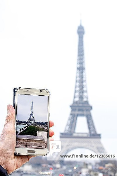 Frau fotografiert den Eiffelturm mit Smartphone  Paris  Ile De France  Frankreich  Europa