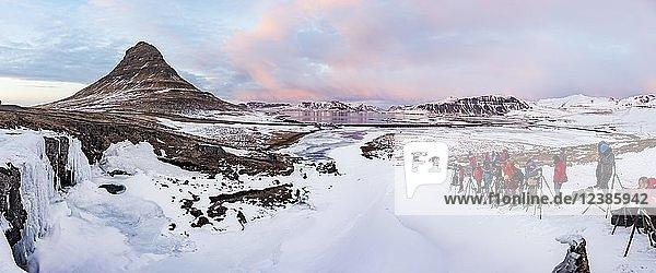 Viele Fotografen fotografieren Berg Kirkjufell mit eingefrorenem Wasserfall Kirkjufellfoss  Wolkenhimmel mit Abendrot  Fjord Grundarfjördur  Westisland  Island  Europa