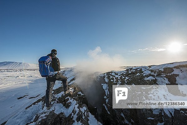 Mountain hiker stands at Continental Rift between North American and Eurasian Plate  Mid-Atlantic Ridge  Rift Valley  Silfra Rift  Krafla  North Iceland  Iceland  Europe