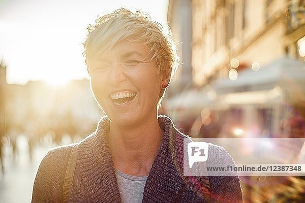 Laughing woman in the city during summer  portrait  backlight