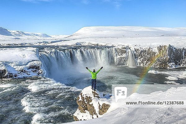 Young man standing on a rock and stretching his arms into the air  waterfall with rainbow  Góðafoss  Godafoss in winter with snow and ice  Norðurland vestra  Northern Iceland  Iceland  Europe