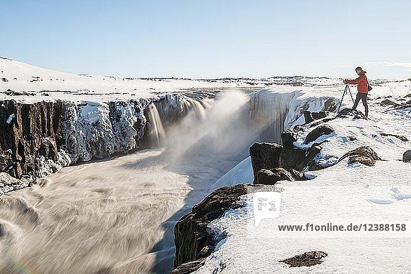 Fotografierender Mann an Abbruchkante des Selfoss Wasserfall im Winter,  Schlucht,  Nordisland,  Island,  Europa