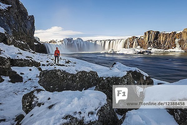 Mann vor Wasserfall Góðafoss  Godafoss im Winter mit Schnee und Eis  Skjálfandafljót Fluss  Norðurland vestra  Nordisland  Island  Europa