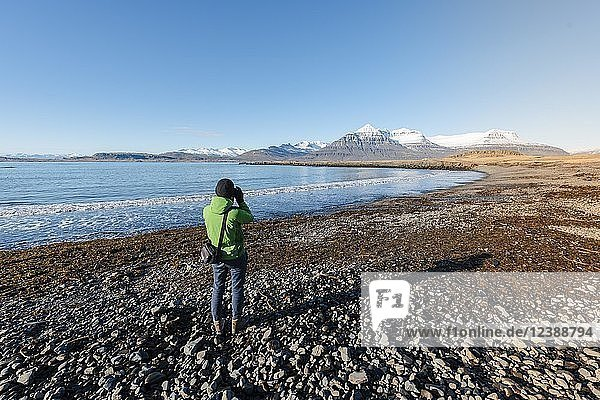 Tourist fotografiert an einem schwarzen Strand am Fjord Berufjörður  Austurland  Ostisland  Island  Europa