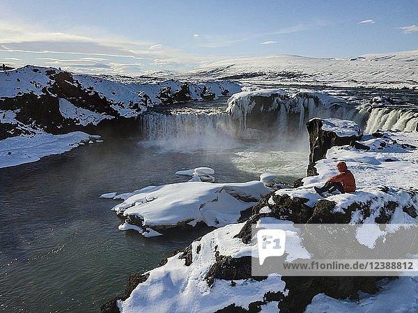 Luftaufnahme  Mann steht vor Wasserfall Góðafoss  Godafoss im Winter mit Schnee und Eis  Norðurland vestra  Nordisland  Island  Europa