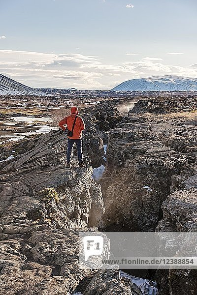 Man stands at Continental Rift between North American and Eurasian Plate  Mid-Atlantic Ridge  Rift Valley  Silfra Rift  Krafla  North Iceland  Iceland  Europe