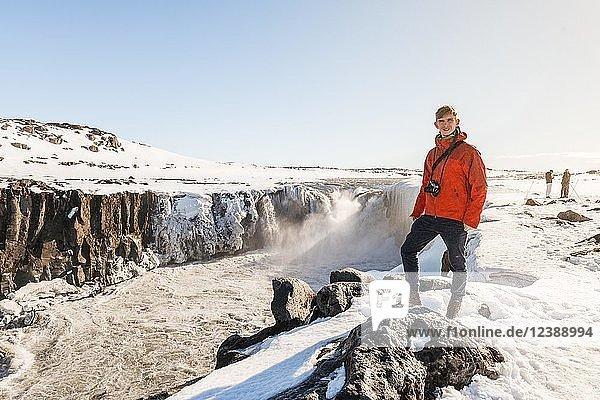 Mann mit Kamera steht an Abbruchkante  Selfoss Wasserfall im Winter  Schlucht  Nordisland  Island  Europa