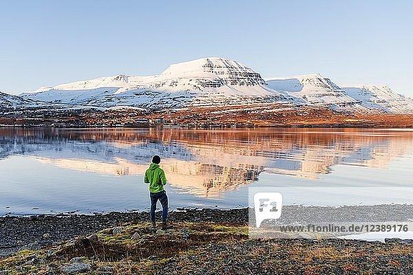 Mann steht am Ufer  Wasserspiegelung der schneebedeckten Berge in einem Fjord  Reyðarfjörður  Ost-Island  Island  Europa